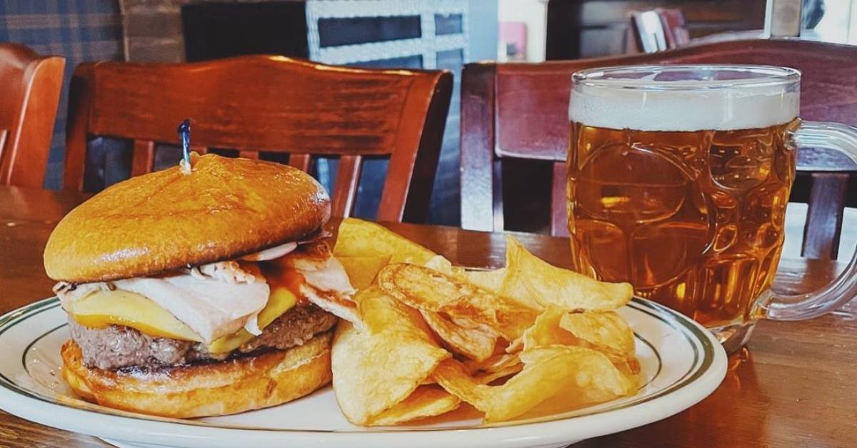 burger and chips on plate and a glass of beer on a table