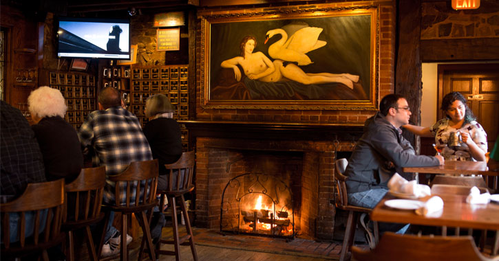 a fireplace roaring in a restaurant with a painting of a naked woman and a swan above it