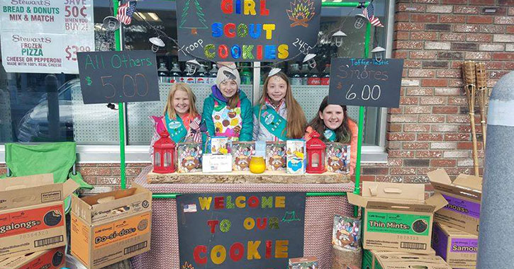 four girl scouts at a cookie booth
