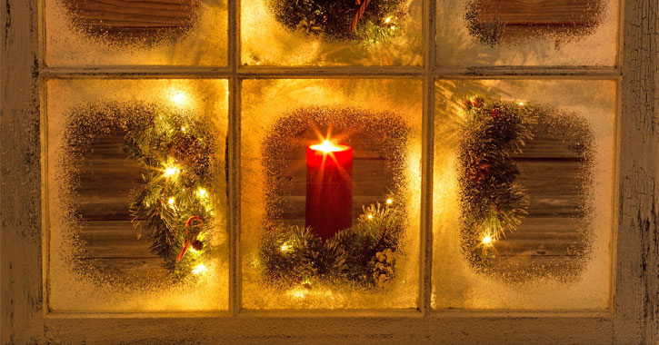 looking into the inside of a window with frosted glass and a red candle burning
