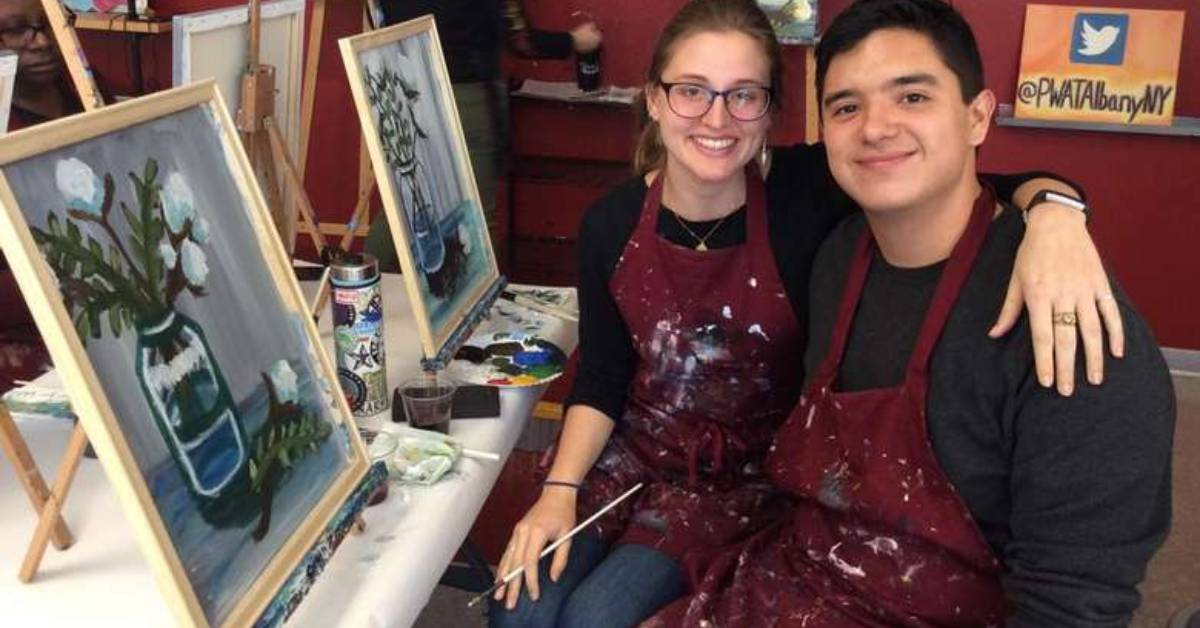 man and woman smiling at paint and sip table