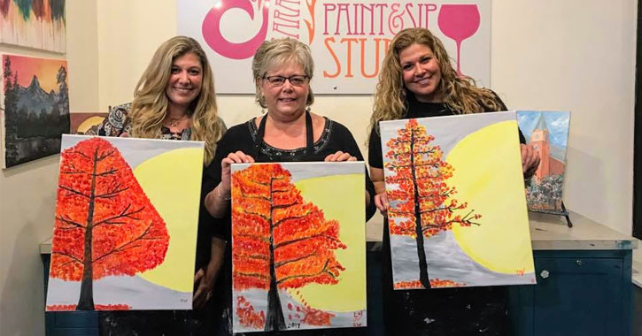 three woman holding up paintings of a tree