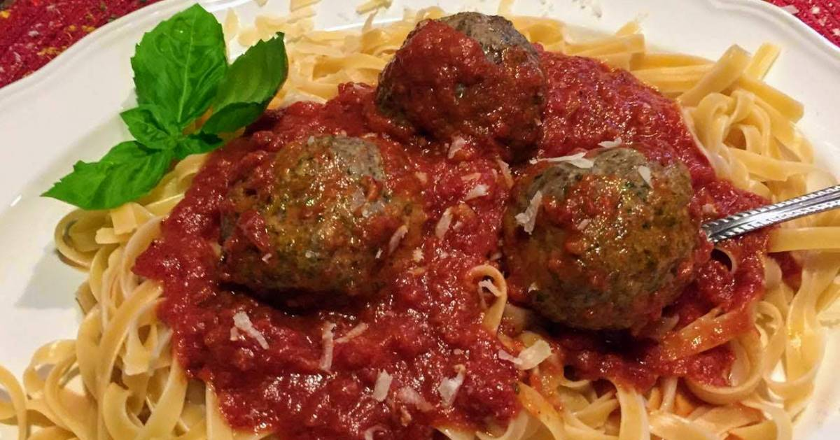 meatballs and pasta with sauce, garnished with basil