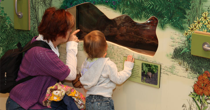 a woman and her kid looking through a hole in the wall at an interactive exhibit