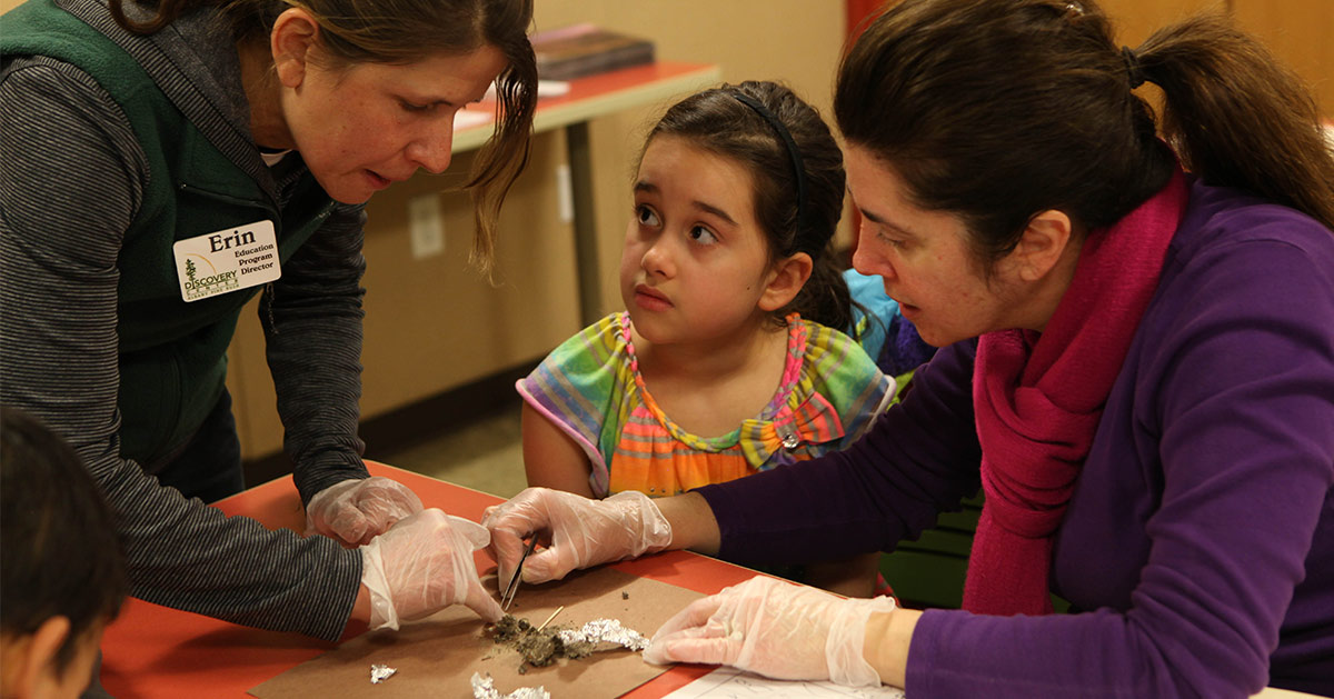 girl participating in an owl pellet lesson taught by an educator