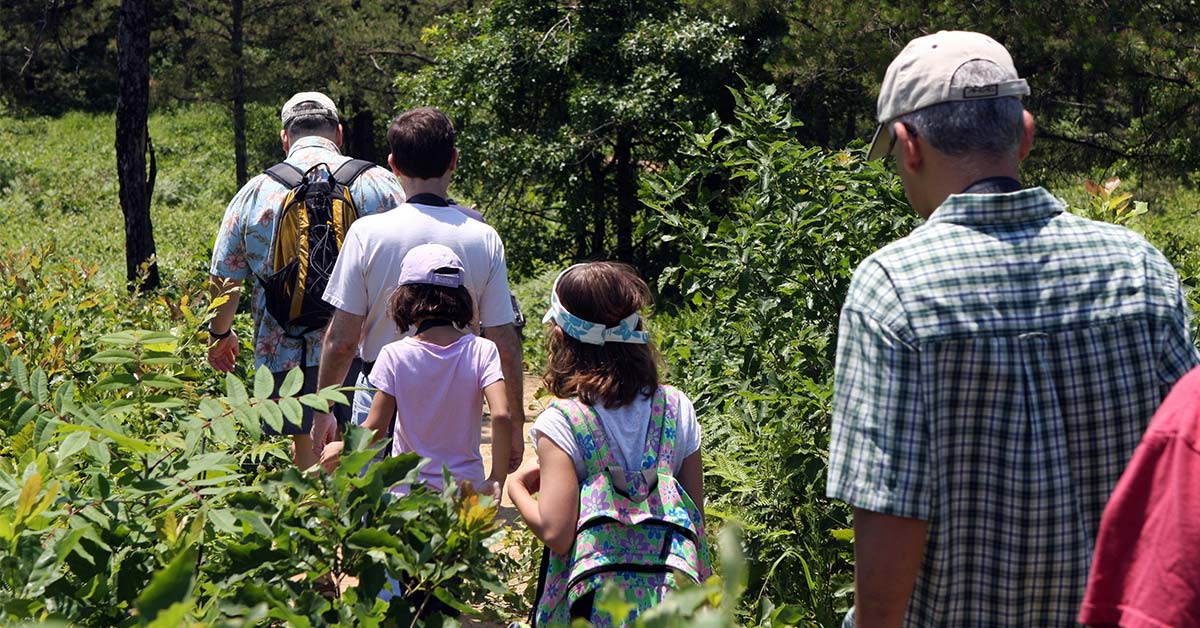 group of adults and kids hiking at the albany pine bush preserve