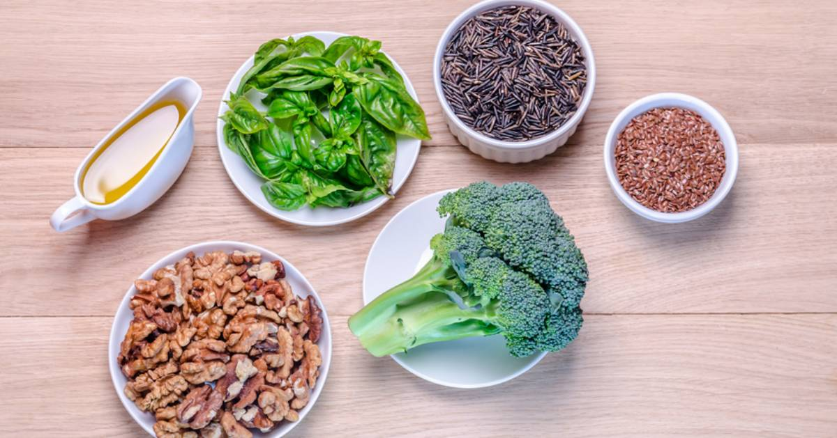 collection of plant-based foods on table like broccoli and walnuts