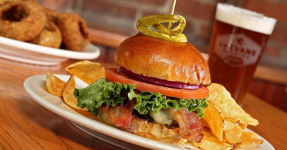 a burger with lettuce, tomato,onion,  bacon, chips on the plate, beer and onion rings in the background
