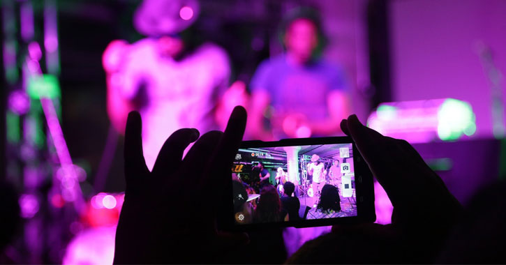 person at concert with purplish lights taking a video of music performers on their phone
