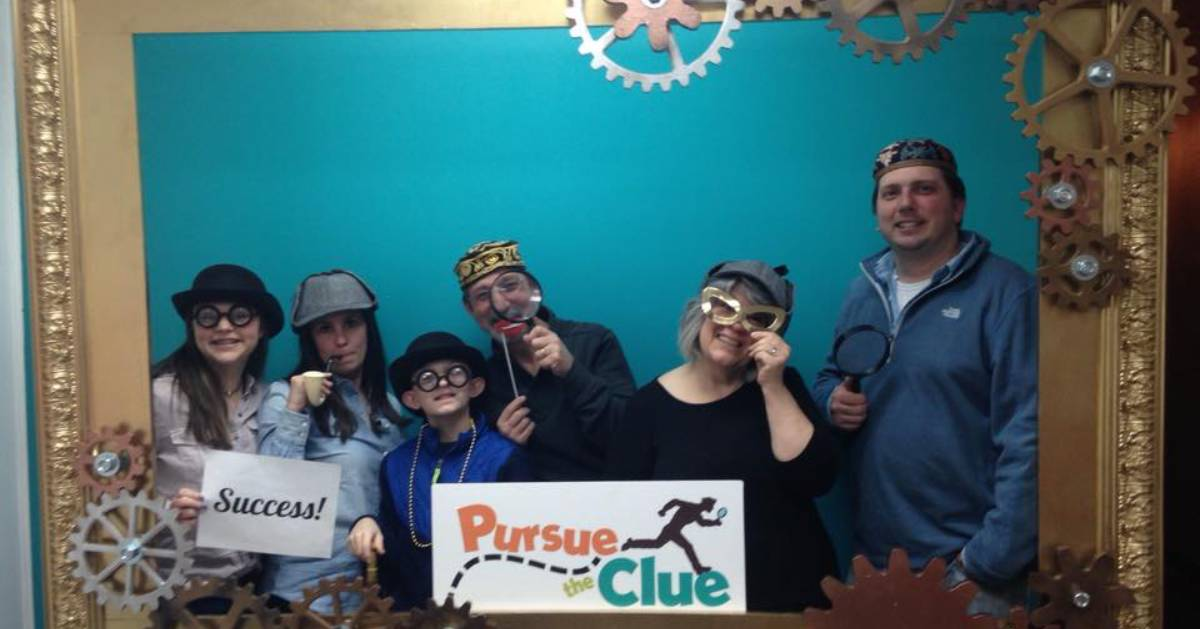 family wearing detective props and holding signs that read success and pursue the clue