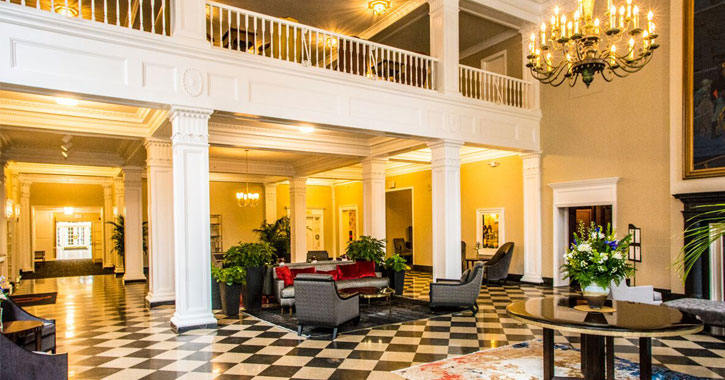 beautiful lobby of The Queensbury Hotel with a black and white checkered floor, white pillars, a chandelier, a plants