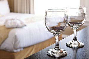 two water glasses on a table with hotel bed in background