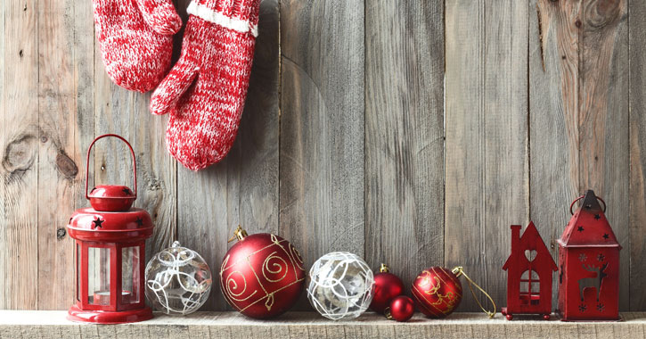 red Christmas decorations along a mantel with a wooden wall, red wool mittens hanging above them