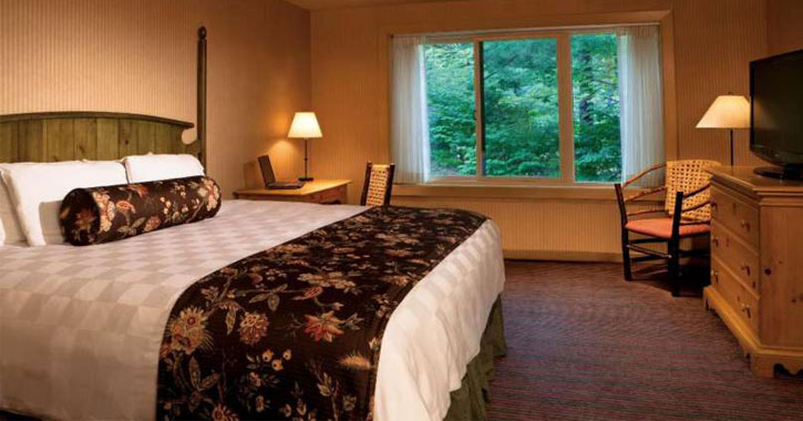 a hotel room with wooden bed and furniture, a window looking out at trees