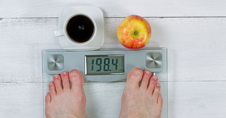 bare feet on a scale that reads 198.2, black coffee and an apple in front of the scale