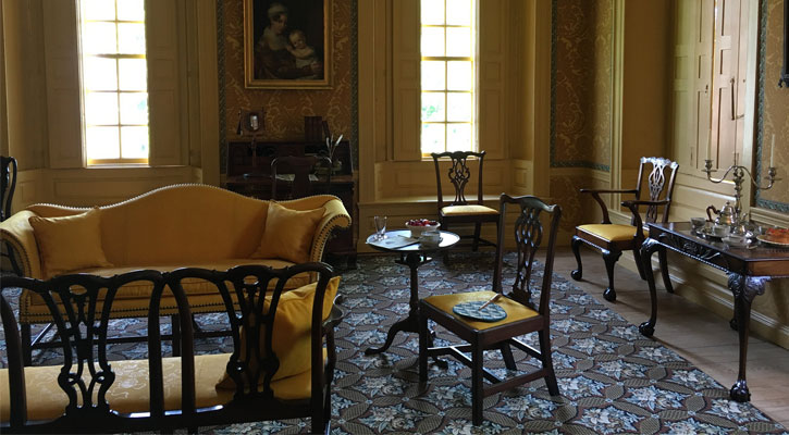 a room in the Schuyler Mansion with a mustard yellow sofa, chairs, blue and gray patterned rug