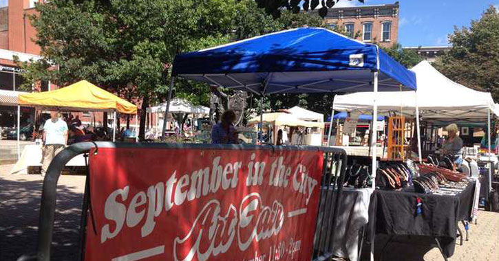 red banner advertising September in the City Art Fair in front of vendor booths