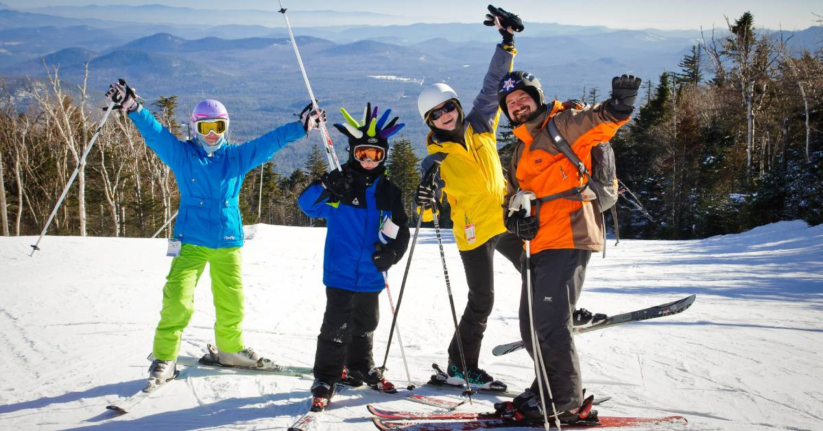 two kids, a woman, and a man in ski gear on mountain