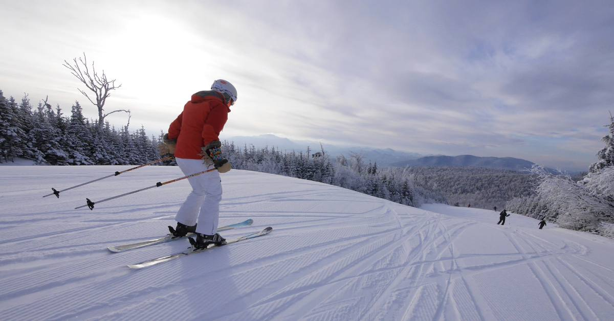 skier in red coat going downhill