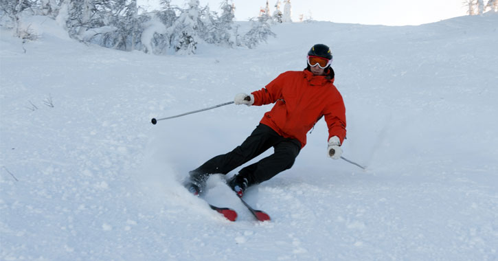 a man dressed in red downhill skiing
