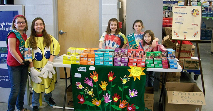 five girl scouts at a cookie booth
