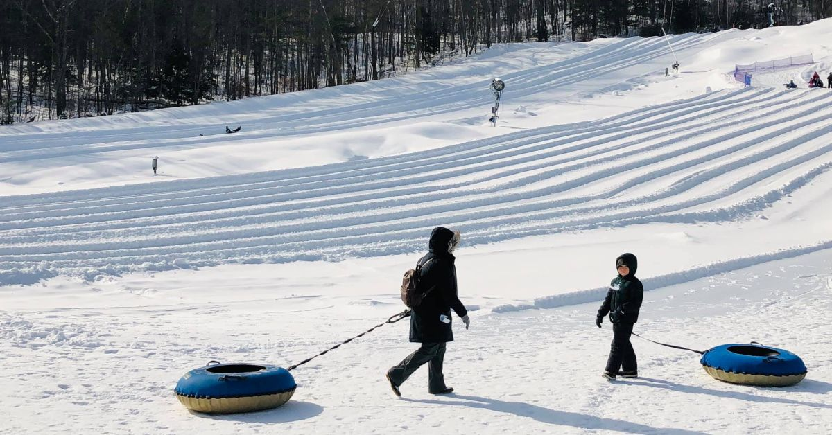 woman and kid with blue snow tubes near a hill