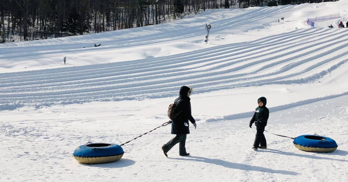 an adult and a kid with snow tubes at a snow tube park