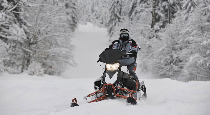 a person snowmobiling surrounded by snow and woods