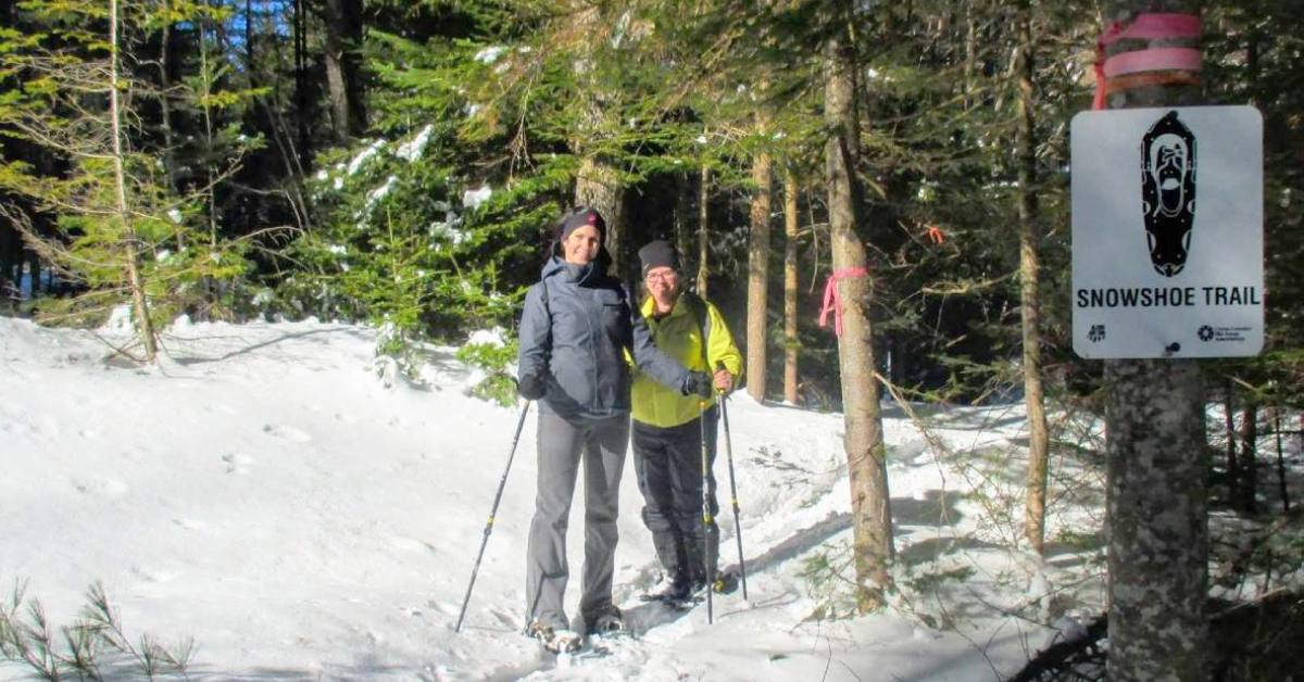 two women wearing snowshoes and smiling