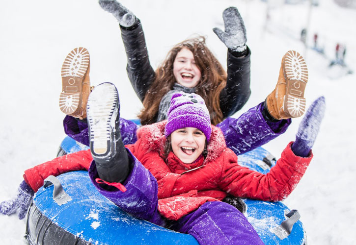two girls laughing while snow tubing