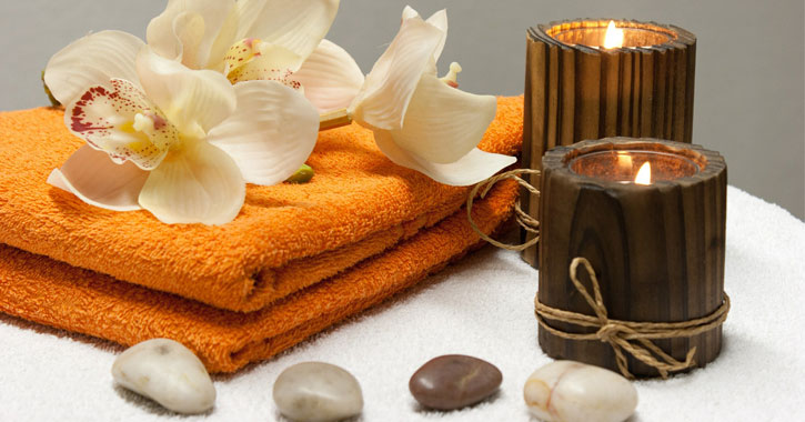 candles and rocks by orange towels with flowers on them