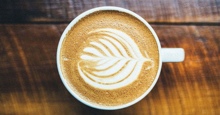 a cup of coffee or latte with a pretty design on the foam