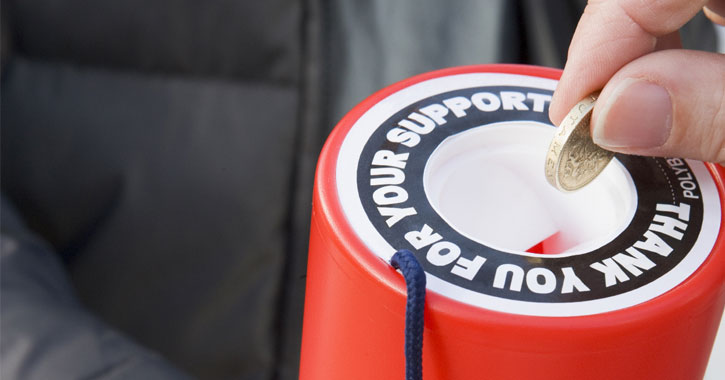 a hand putting a coin into a tube that says thank you for your support