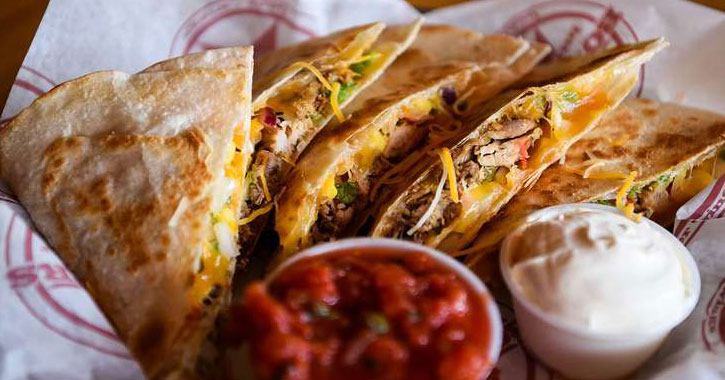 quesadillas spread out with salsa and sour cream for dipping
