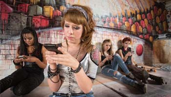 four teen girls in front of a graffitied wall, all looking at phones