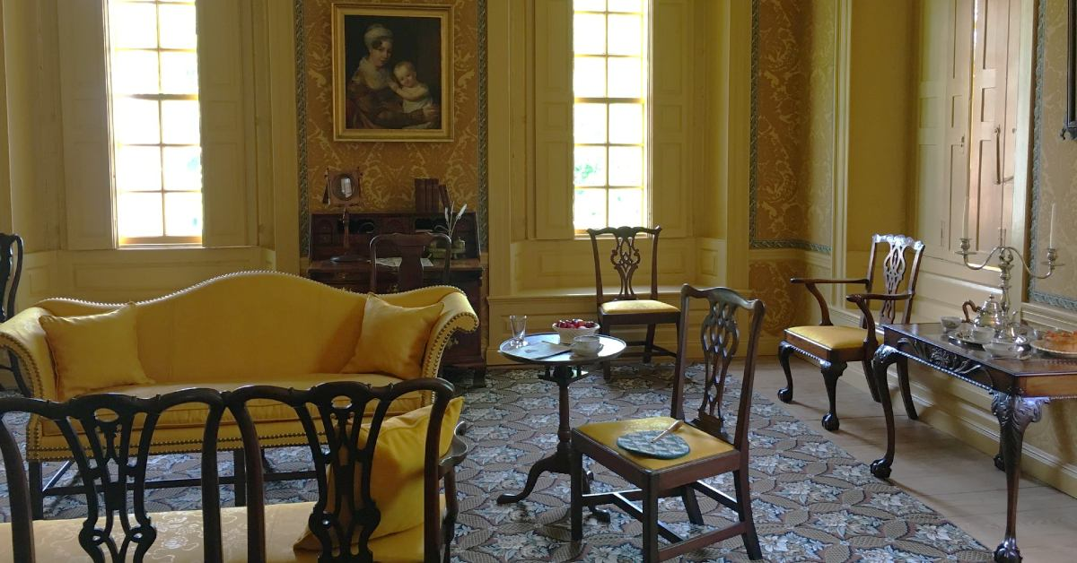 a room with antique furniture and yellow walls