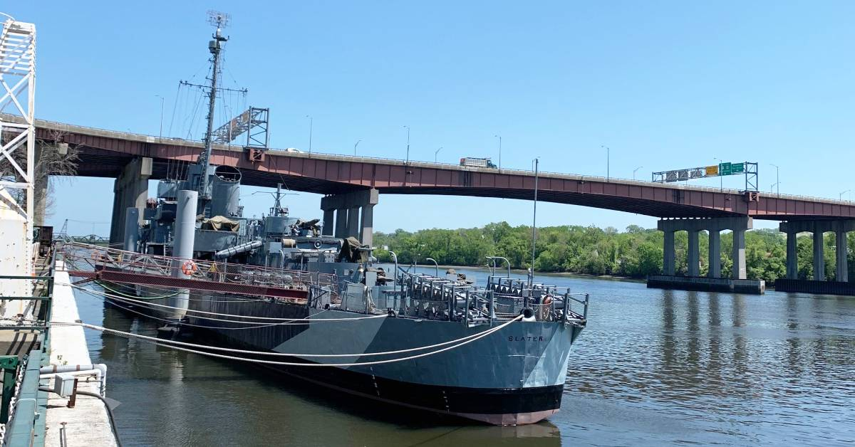 a large warship on a river docked near land