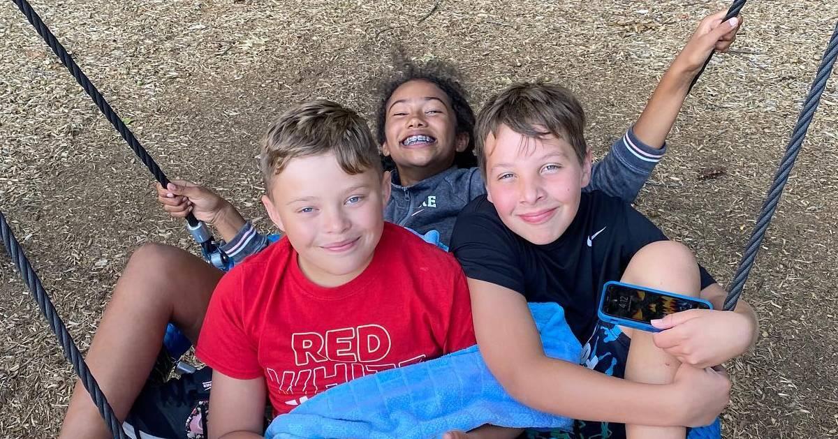 three camp kids on a tire swing