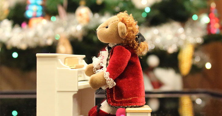 a tiny stuffed bear playing music on a tiny piano with a blurred christmas tree int