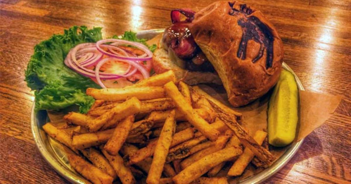a plate with a burger and fries, the burger has an image of a moose on it