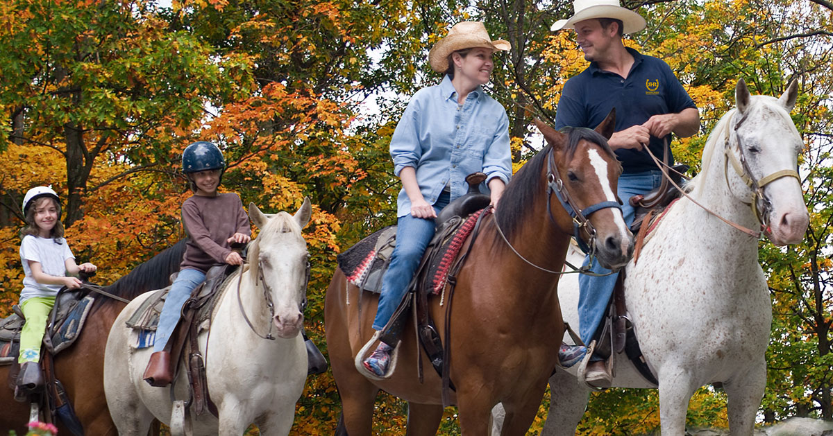 family of four horseback riding