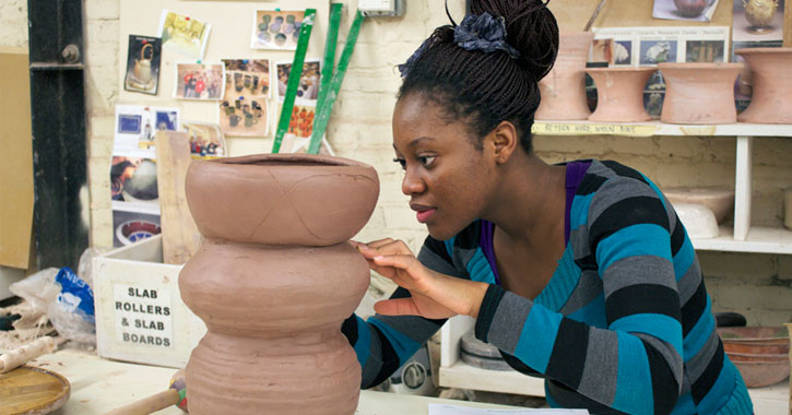 a woman working on pottery