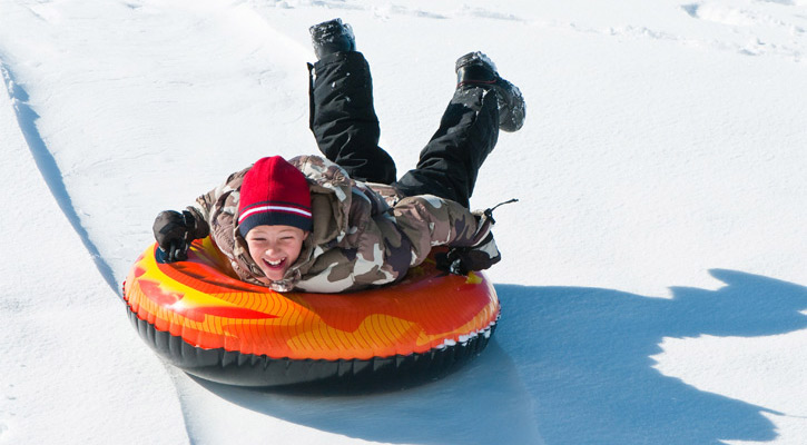 a young boy snow tubing down a hill, grinning