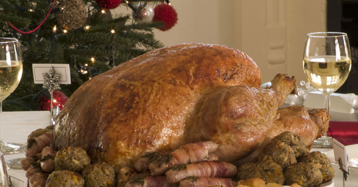 a whole turkey on the dinner table surrounded by appetizers and stuffing with glasses of white wine to each side and the Christmas tree behind
