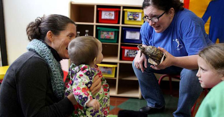 a woman showing a toddler a turtle