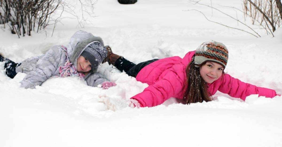 two kids laying in snow