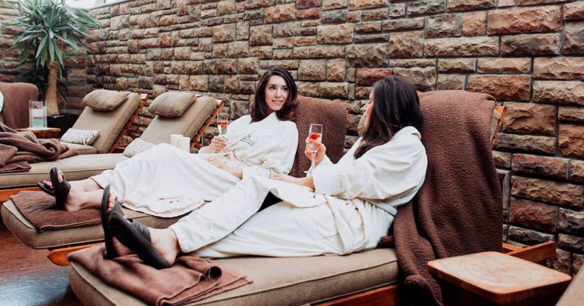 two women relaxing on spa recliner chairs
