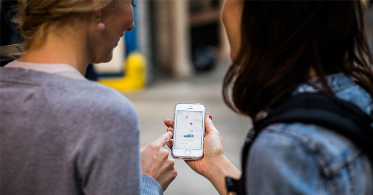 two women looking a Lyft app on a phone