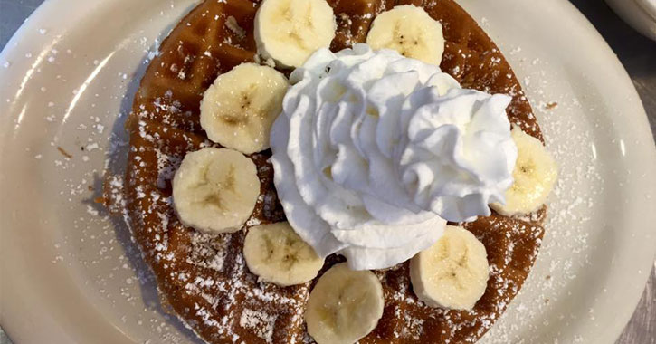 waffles with banana slices and whipped cream