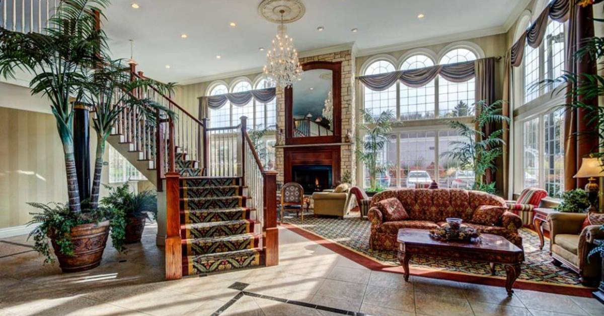large hotel lounge area with staircase and fireplace